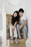 Retrato integral de los pares jovenes que se sientan en escalera Imágenes de archivo libres de regalías