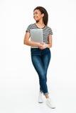 Retrato integral de un adolescente africano sonriente que sostiene el ordenador portátil Imagenes de archivo