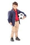 Retrato integral de un colegial que sostiene un balón de fútbol Imágenes de archivo libres de regalías