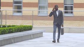 Retrato integral de un hombre joven feliz que camina y que habla en el teléfono móvil, cámara lenta almacen de video