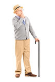 Retrato integral de un hombre mayor dudoso con el bastón en thoug Fotografía de archivo libre de regalías