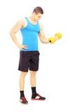 Retrato integral de un individuo joven que levanta una pesa de gimnasia Fotografía de archivo