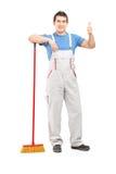 Retrato integral de un limpiador masculino con una escoba que da el pulgar Imagenes de archivo