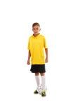 Retrato integral de un pequeño futbolista en una camiseta amarilla, pantalones cortos negros aislada en un fondo blanco Imagenes de archivo
