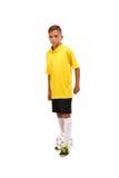 Retrato integral de un pequeño futbolista en una camiseta amarilla, pantalones cortos negros aislada en un fondo blanco Foto de archivo libre de regalías