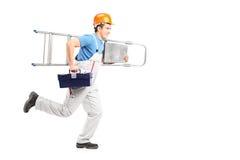 Retrato integral de un reparador que corre con una escalera Imagenes de archivo