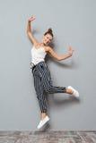 Retrato integral de un salto lindo alegre de la mujer Foto de archivo libre de regalías