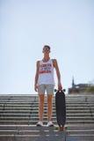 Retrato integral de un skater Adolescente con un monopatín en un fondo del cielo Concepto que anda en monopatín Copie el espacio Fotografía de archivo