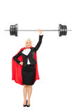 Retrato integral de un super héroe femenino que levanta un barbell Foto de archivo