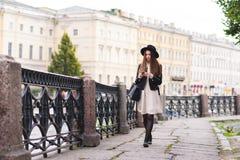 Retrato integral de un turista femenino joven que usa el teléfono elegante para la navegación durante caminar en la calle en el a Imagenes de archivo
