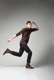 Varón de la moda de los jóvenes que salta en fondo gris Fotos de archivo