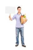 Retrato integral de un varón que sostiene una bolsa de papel y una cacerola en blanco Fotografía de archivo