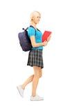 Retrato integral de una colegiala que lleva a cabo los libros de texto y el backp Foto de archivo libre de regalías