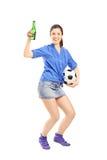 Retrato integral de una fan femenina feliz que sostiene una botella de cerveza Imagen de archivo libre de regalías