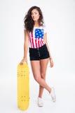 Retrato integral de una muchacha adolescente que sostiene el monopatín Foto de archivo