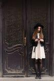 Retrato integral de una muchacha de moda joven del inconformista con el pelo moreno largo que charla en su teléfono de célula Fotos de archivo libres de regalías