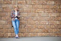 Retrato integral de una muchacha del estudiante contra la pared de ladrillo Fotografía de archivo