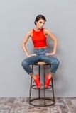 Retrato integral de una muchacha seria que se sienta en silla Imagen de archivo libre de regalías
