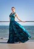 Retrato integral de una mujer hermosa en un vestido esmeralda que agita largo en un fondo del cielo azul foto de archivo libre de regalías