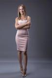 Retrato integral de una mujer rubia atractiva en vestido de la moda con las manos en caderas Fondo gris Concepto del lenguaje cor imagenes de archivo