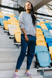 Retrato integral del adolescente afroamericano serio con los auriculares que se colocan en las escaleras del estadio Fotografía de archivo libre de regalías