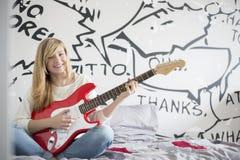 Retrato integral del adolescente que toca la guitarra en dormitorio Imagen de archivo