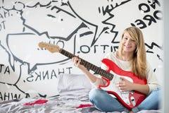 Retrato integral del adolescente que toca la guitarra en dormitorio Imagen de archivo libre de regalías
