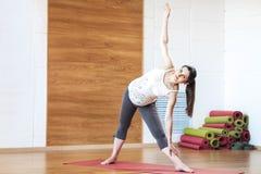 Retrato integral del modelo embarazada joven de la aptitud en la ropa de deportes que hace la yoga, pilates que entrenan, ejercic Fotos de archivo