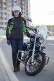 Retrato integral del motorista femenino en el equipo de la seguridad que se coloca cerca de la bici clásica en el camino urbano fotografía de archivo