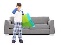 Retrato integral del muchacho soñoliento en los pijamas que se colocan en frente Fotos de archivo