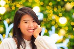 Retrato interior de la mujer bastante asiática con el fondo de la luz de la Navidad Imagen de archivo