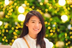Retrato interior de la mujer bastante asiática con el fondo de la luz de la Navidad Fotografía de archivo