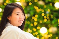 Retrato interior de la mujer bastante asiática con el fondo de la luz de la Navidad Fotografía de archivo libre de regalías