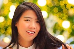 Retrato interior de la mujer bastante asiática con el fondo de la luz de la Navidad Imagen de archivo libre de regalías