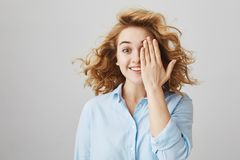 Retrato interior del estudiante caucásico hermoso emocionado con la mitad corta de la cubierta del pelo rizado de la cara con la  Fotografía de archivo