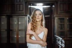 Retrato interior del verano de la muchacha bastante linda de los jóvenes Mujer hermosa que presenta al lado de puerta del cuento  Imágenes de archivo libres de regalías