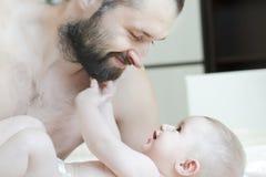 Retrato interno da família do pai feliz que joga com sua criança do bebê foto de stock