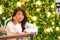 Retrato interno da mulher asiática bonita com fundo da luz de Natal Fotografia de Stock