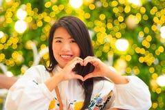 Retrato interno da mulher asiática bonita com fundo da luz de Natal Imagem de Stock