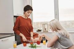Retrato interno da mulher quente atrativa que senta-se no tomotoe do corte da tabela quando sua amiga beber o suco na cozinha foto de stock