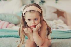 retrato interno de 5 anos bonitos tristes da menina idosa da criança que senta-se na cama Fotografia de Stock