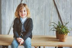 Retrato interno de 5 anos de menino idoso com o cabelo longo que senta-se na tabela Foto de Stock