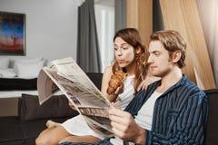 Retrato interno de pares bonitos no jornal da leitura do amor no apartamento, assento no sofá, pyjamas vestindo girlfriend fotografia de stock