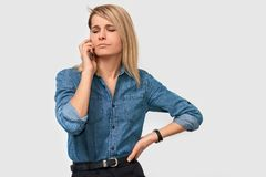 Retrato interno do conselheiro caucasiano sério da mulher na camisa da sarja de Nimes, tendo na conversação de telefone celular a fotos de stock