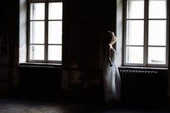 Retrato interno do verão da menina consideravelmente bonito dos jovens Mulher bonita que levanta ao lado de duas janelas dentro d imagens de stock royalty free