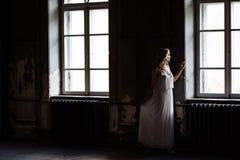 Retrato interno do verão da menina consideravelmente bonito dos jovens Mulher bonita que levanta ao lado de duas janelas dentro d imagem de stock royalty free