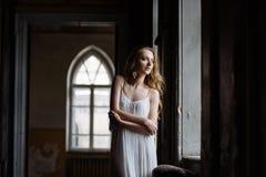 Retrato interno do verão da menina consideravelmente bonito dos jovens Mulher bonita que levanta ao lado da janela do conto de fa fotos de stock