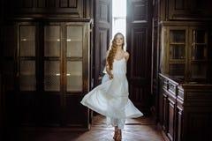 Retrato interno do verão da menina consideravelmente bonito dos jovens Mulher bonita que levanta ao lado da porta do conto de fad imagens de stock