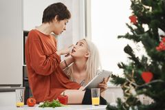 Retrato interno dos pares sensuais e macios novos de meninas, expressando o amor e a atração ao sentar-se na cozinha e Fotos de Stock