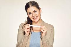 Retrato isolado da jovem mulher de sorriso que guarda o teste grávido Imagens de Stock